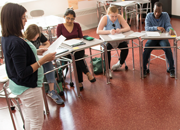 Teacher standing and instructing four students sitting at desks.