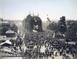 A scene of Emperor Meiji being welcomed back to Tokyo in 1895. A large crowd gathers in the street and flies the flag of Japan.