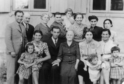 A family of 16 people, including a few children, pose in front of a house.