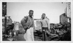 Two young men stand in front of the remains of the house and shop belonging to them after the occupation of Nanjing.