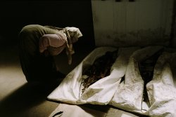 A woman bends over to examine two body bags full of bones lining a wall.