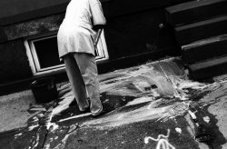 A woman standing next to a bucket scrubs a soap-covered sidewalk with a mop.