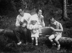 Photo of Otto and Maria Ginz sitting on a log with children Petr Ginz and Eva Ginzova.