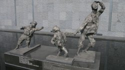A statue featuring a woman running, holding hands with a young girl while another young girl trails behind them. All show expressions of fear and distress on their faces.