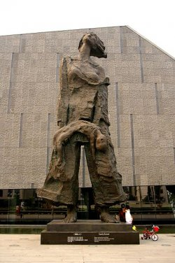 A large statue of a woman holding a an unconscious child.