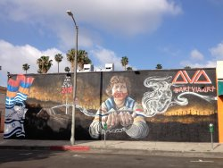 """A mural features an elderly woman with a piece of tape over her mouth with """"1915"""" written on it."""