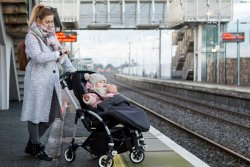 Woman with a baby in stroller waiting for a train.