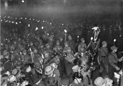 Men parade through the street at night carrying torches.