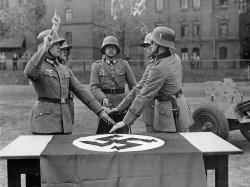 Three men in military uniforms hold one hand over the Nazi flag and raise the other.