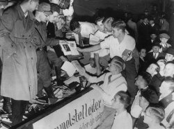 Crowds of young men are adding books to a dumpster to be destroyed at a Berlin book-burning.
