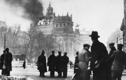 The German Reichstag building in flames, with men looking on.