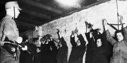 A man in uniform stands before a line of men and women against a brick wall with their hands up.