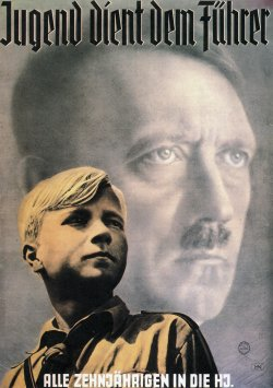 A boy in a Nazi Youth uniform in the foreground and an image of Adolf Hitler in the background.