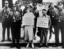 Seven men in uniform stand around a man and woman who have signs around their necks.
