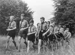 A group of boys in Hitler Youth uniforms walk through a field.