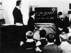 Boys stand in front of the class around a chalkboard on which a Star of David is drawn.