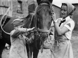 Woman and young boy in a Nazi youth uniform with a horse.