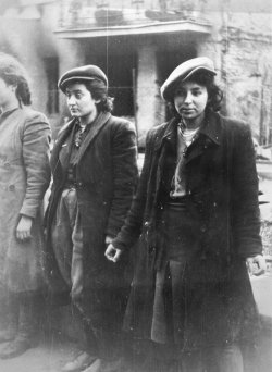 Three women with long coats and berets.