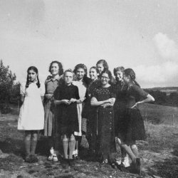 Group of standing girls smiling.