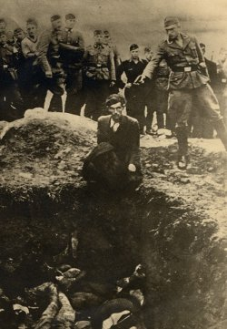 Nazi soldier holds gun to a man's head who is kneeled next to a ditch full of bodies.