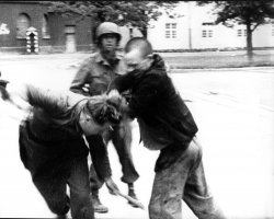 An inmate of Dachau concentration camp strikes a German soldier after camp liberation in 1945.