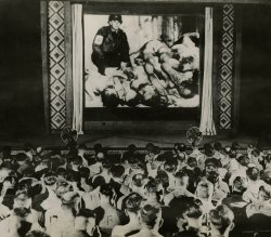A movie theatre full of former soldiers view an image of dead bodies on the screen.