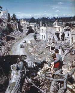 Two boys sit on a branch in the foreground looking out at destroyed buildings and countryside.