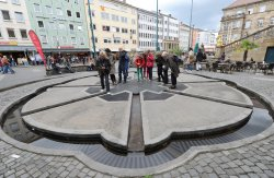 People stand in the center of a fountain built in the ground into the middle of a plaza.