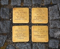 Four golden squares with inscriptions are built into the sidewalk.