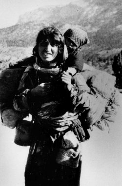 A black and white photo of an Armenian woman carrying her child on her back.