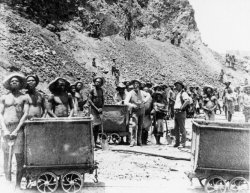 Large line of black South Africans standing with shovels next to mine carts with some black South Africans working on the hillside behind them.