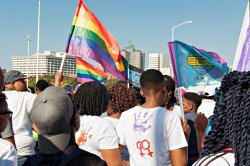 People marching in the Gay Pride Festival in Johannesburg carrying flags and signs.