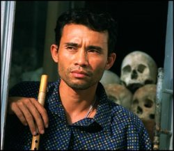 Arn Chorn-Pond stands in a doorway with his flute in hand. A pile of skulls are visible behind him.