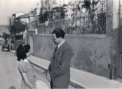 A middle-aged man and his teenage daughter gaze into each other's faces, while standing on the side of a residential city street in France.