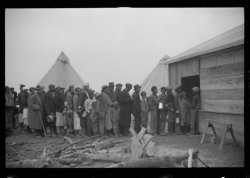 A long line of African Americans entering a building to receive food.