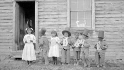 Young boys in top hats and girls in dresses are standing in a line, each holding up a letter.