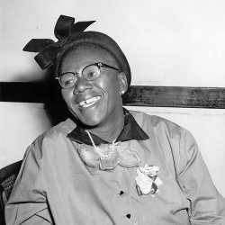 Seated and smiling middle-aged black South African woman with glasses.