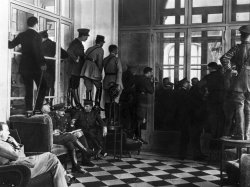 Officers stand on chairs and tables to see over the heads of a crowd to view the signing of the Treaty of Versailles.