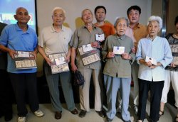 A group of elderly Nanjing massacre survivors hold photos and paperwork in their hands and pose for the camera. Photo taken July 6, 2013.