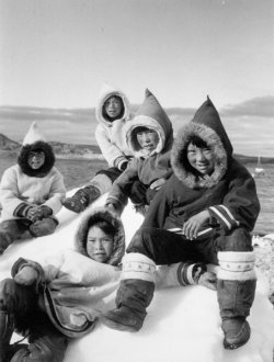 Young boys sitting on snow wearing hooded coats lined with fur and boots.