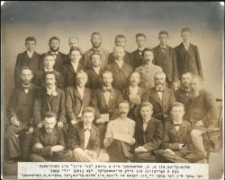 A group of 26 men pose in four rows. Sholem Aleichem sits in the center of the front row.