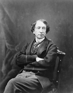 Seated portrait of John A. Macdonald with his arms folded.