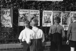 Four young German boys view Der Stürmer and other Nazi propaganda displayed on a fence along the street.