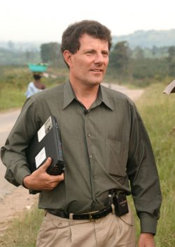 A picture of journalist Nicholas Kristof holding a laptop under his arm.