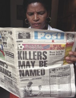 "Black South African woman reading a newspaper with the front page headlines ""KILLERS MAY BE NAMED"""