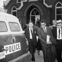 James Lawson, flanked by two police officers, is led to a police vehicle while a crowd looks on behind him.