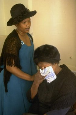 Two black South African women. Younger woman is standing, wearing a blue dress and black shawl and hat, and is consoling the sitting older woman who is crying into a handkerchief