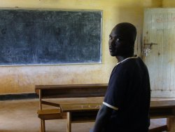 Jimmy Otim standing in front of a table and chalkboard.