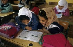 In the foreground, two girls wearing veils work on an assignment together at their desks. In the background, other students also work at their desks.