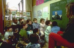 A group of young students sit in front of a chalkboard as their teacher delivers their lesson.